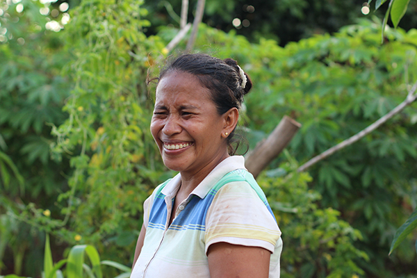 Heni, a woman and mother in Rote Island, Indonesia, smiles at her community garden.