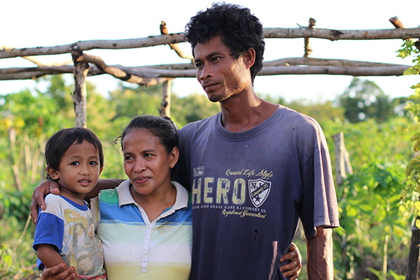 Heni (middle) with her husband and son Yardi stand together outside their community garden. © Sarah Gray