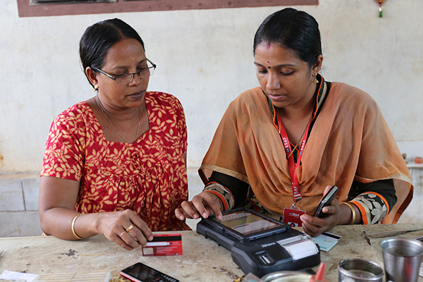 A loan officer helps a woman process her small loan with the help of a tablet in India.