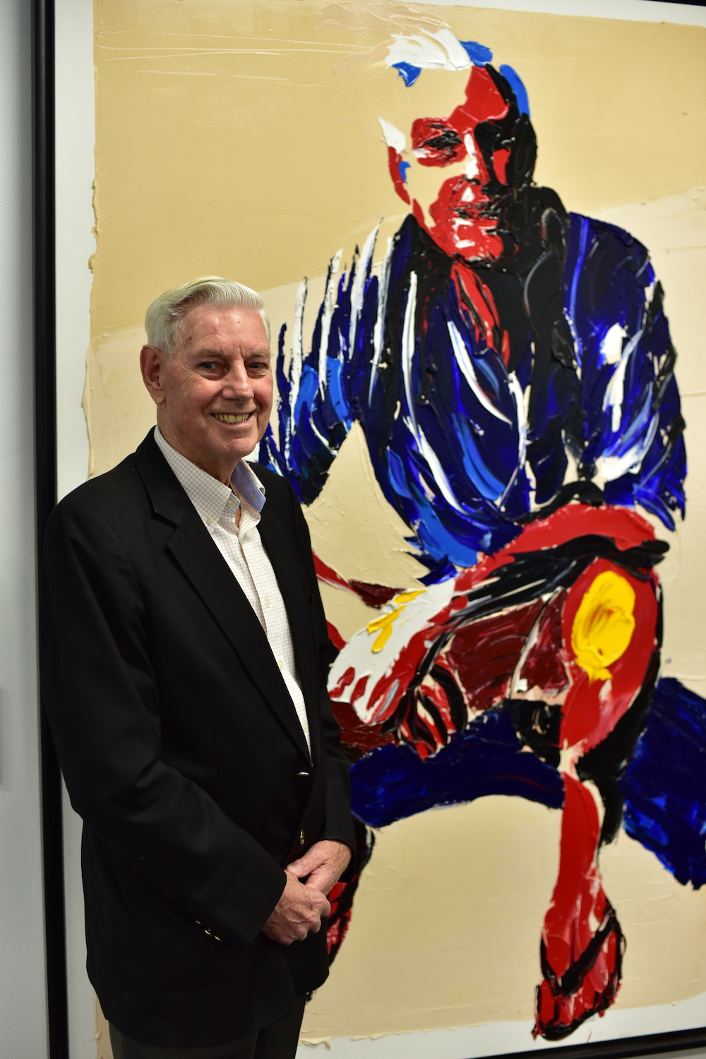 David Bussau standing in front of his Archibald Prize portrait