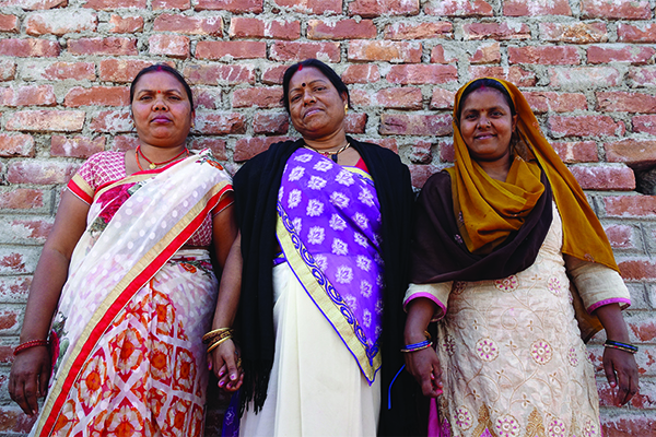 Three women Community Health Leaders hold hands in Bihar, India.