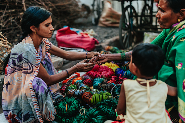 A woman kneels at her market stall in India and helps a customer try on a bangle