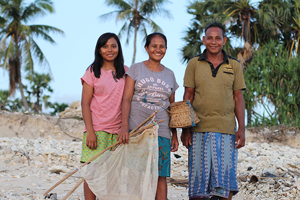 Marce stands on the beach holding a fishing next with her daughter and husband.