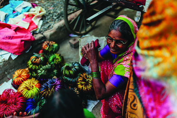 A smiling customer browses Ujjawala's market stall of bangles.