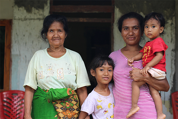 A mother holds her two children standing next to their grandmother, Holoama, Indonesia.