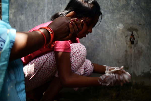 A girl is taught how to wash her hands by a Community Health Leader, Uttar Pradesh, India. Photo: Matthew Smeal