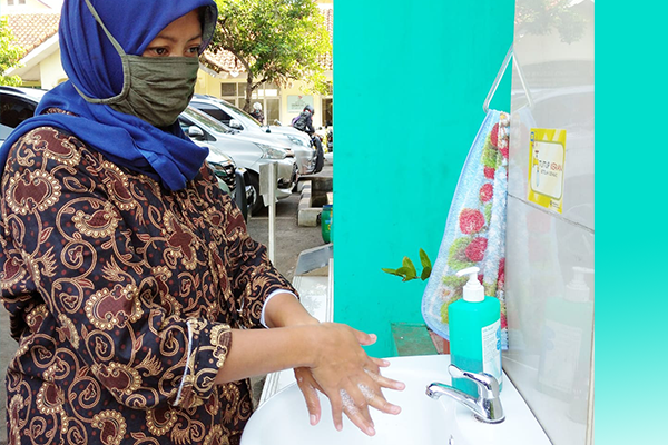 Oneh, a health leader in Indonesia, demonstrates good handwashing techniques.